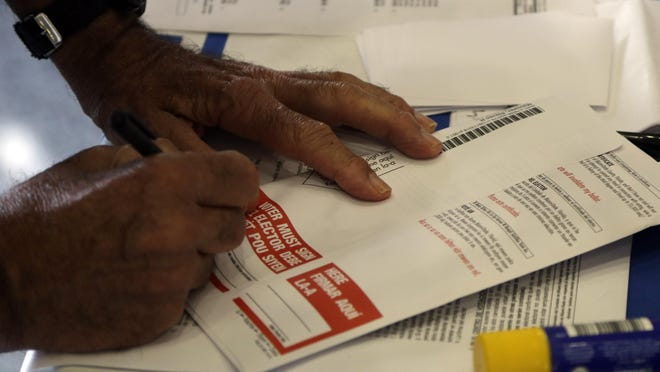 A man signs his absentee ballot in a file photo from Miami.