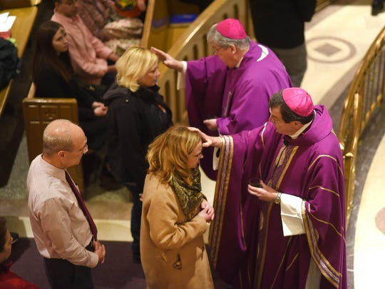 Archbishop Allen Vigneron, bottom, and Bishop Gerald Battersby place the ash on parishioners during Ash Wednesday Mass at St. Aloysius in Detroit on Wednesday.
