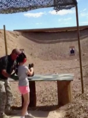 In this Aug. 25, 2014, image made from video provided by the Mohave County Sheriff's Office , firing-range instructor Charles Vacca shows a 9-year-old girl how to use an Uzi. Vacca, 39, was standing next to the girl on Monday at the Last Stop range in Arizona, south of Las Vegas, when the girl squeezed the trigger, causing the Uzi to recoil upward and shoot Vacca in the head.