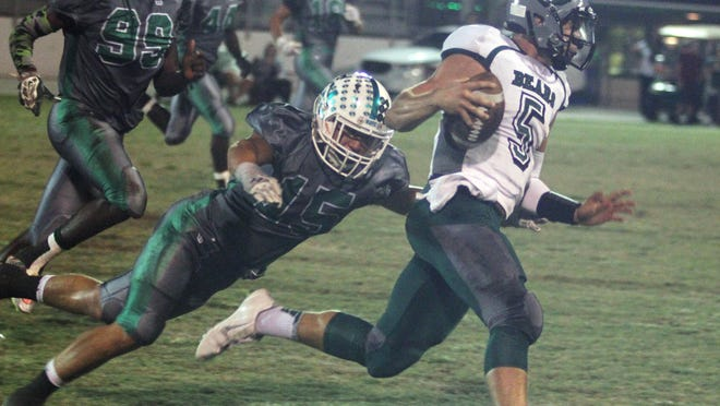 Palmetto Ridge quarterback Cody Young runs the ball as Matt McQuinn attempts the tackle during a playoff game against Fort Myers on Friday, November 13, 2015, at Fort Myers High School.