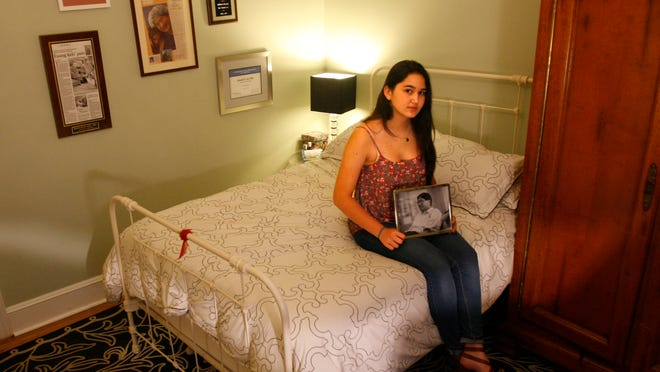 Genevieve Liu holds a photo of her father, Don Liu, in her room in Chicago. The photo of him was taken about a month before he drowned in Lake Michigan in 2012 trying to help two children get to safety. Genevieve, now 15, says she keeps the photo nearby because she knows it captures a moment when her father was looking at her at her bat mitzvah.