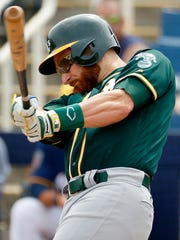 Oakland's Jonathan Lucroy hits against the Milwaukee Brewers during the first inning of a spring training baseball game.