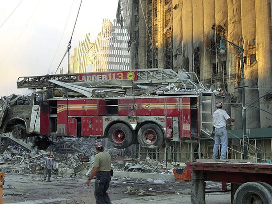 The wreckage of FDNY Ladder Truck 113 is hoisted onto a flat-bed truck in the shadow of Ground Zero on Sept. 13, 2001.
