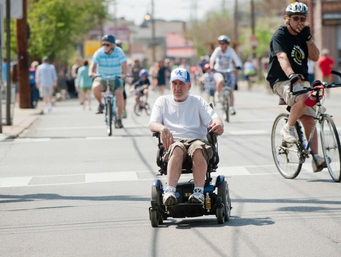 Ronnie Burnett wheels himself down Frankfort Ave. The thoroughfare was closed to vehicular traffic between Stilz Avenue and Pope Street, for the city-sponsored CycLOUvia. Frankfort Avenue became a paved linear park, where residents and visitors biked, walk, skated, danced, and shopped in a car-free environment. 13 April 2013