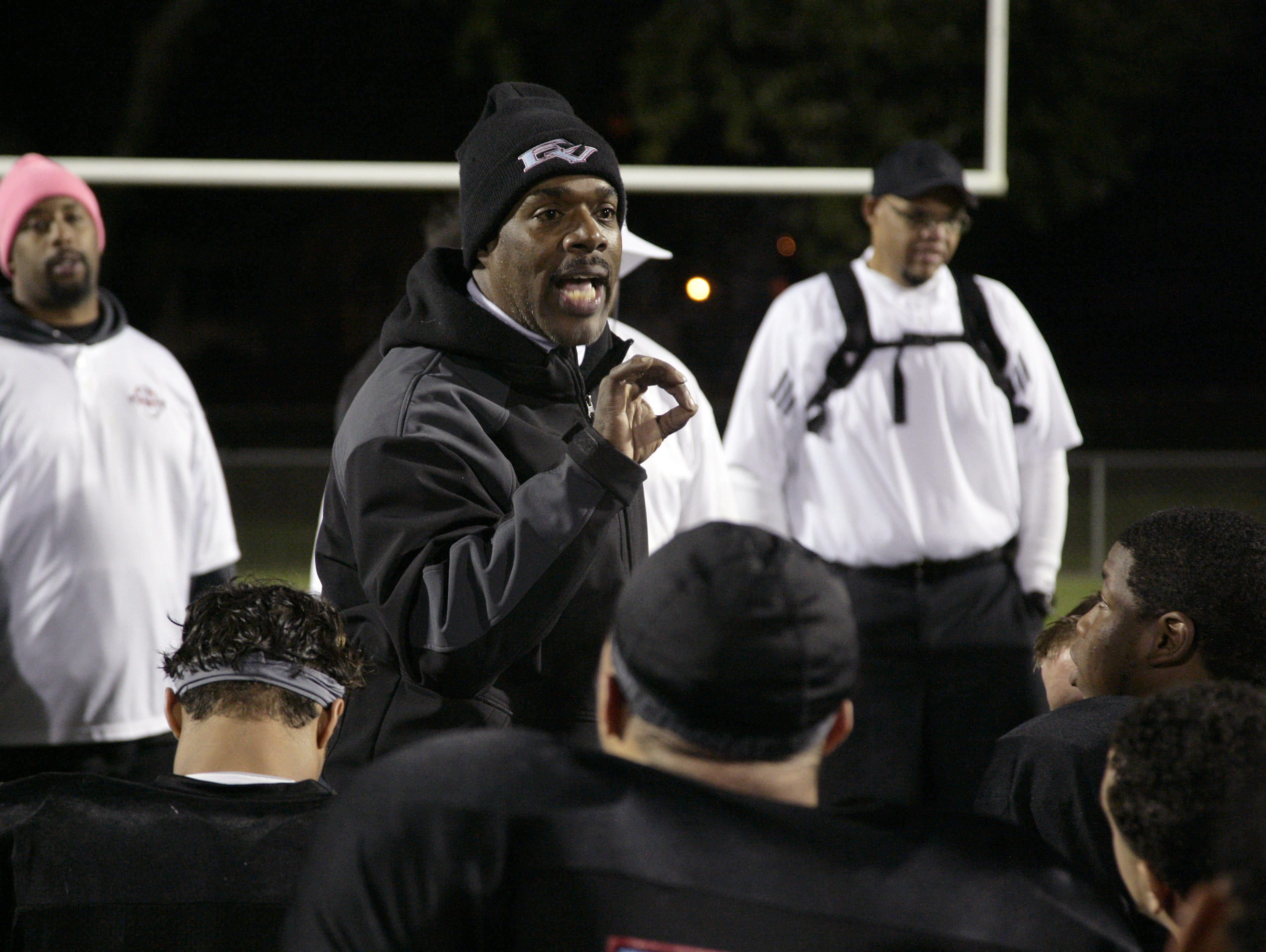 Everett coach Marcelle Carruthers talks to his team following a 38-24 win over Grand Ledge Friday, Oct. 10, 2014, in Lansing, Mich.