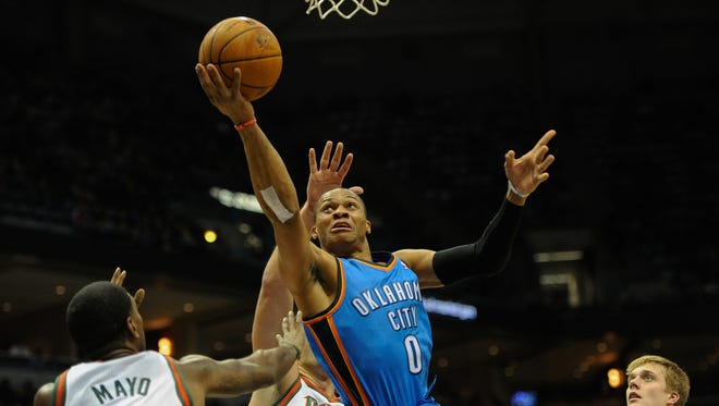 Oklahoma City Thunder guard Russell Westbrook (0) shoots a basket against Milwaukee Bucks guard O.J. Mayo (00) and center Zaza Pachulia (27) in the first quarter at BMO Harris Bradley Center.
