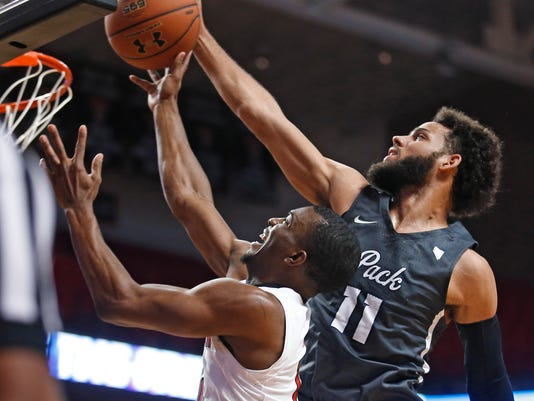 Nevada's Cody Martin (10) fouls Texas Tech's Keenan Evans (12) on a shot during the first half an NCAA college basketball game Tuesday, Dec. 5, 2017, in Lubbock, Texas. (AP Photo/Brad Tollefson)