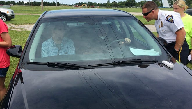 """Capt. Ty Conger, from right, checks on Fremont Police Chief Dean Bliss and News-Messenger reporter Daniel Carson during the """"Beat the Heat"""" event to raise awareness of leaving children and animals unattended in hot vehicles."""