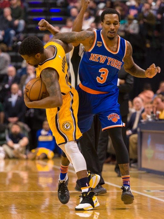 Indiana Pacers guard Aaron Brooks (00) and New York Knicks guard Brandon Jennings (3) become entangled during the second half of an NBA basketball game, Saturday, Jan. 7, 2017, in Indianapolis. (AP Photo/Doug McSchooler)