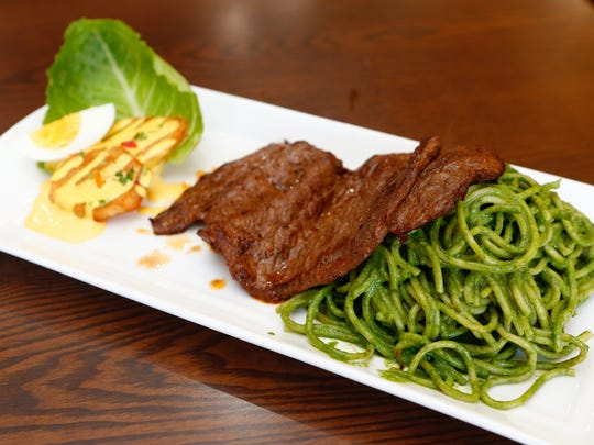 Hanger steak served with Tallarines Verdes (Spaghetti in a Peruvian pesto sauce) at Delicias del Jireh in White Plains on Wednesday, March 22, 2017.