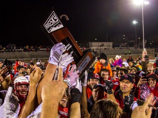 Southern Utah players raise the Big Sky championship trophy after defeating NAU, Saturday, Nov. 21, 2015.
