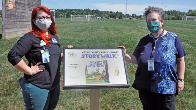 Wayne County Children's Department Manager Hayley Tracy-Bursley, left, and Assistant Director Susan Roberts stand with the first story board located in the northern most parking lot south of the soccer fields on the Kinney property on Burbank Road in Wooster.