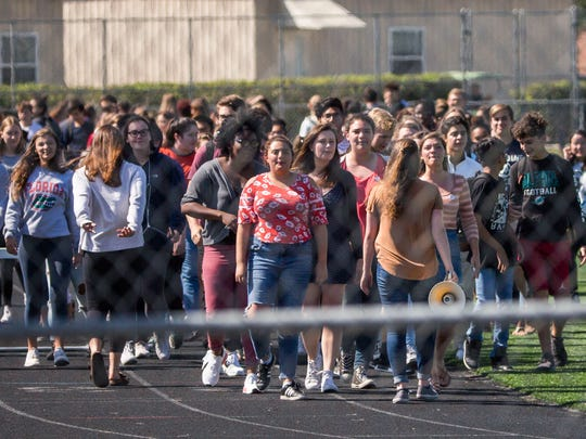 A large group of students chant and walk a lap around their school track during the National School Walkout to protest legislative inaction on gun laws on the 19th anniversary of the Columbine High School massacre at Gulf Coast High School on Friday, April 20, 2018.
