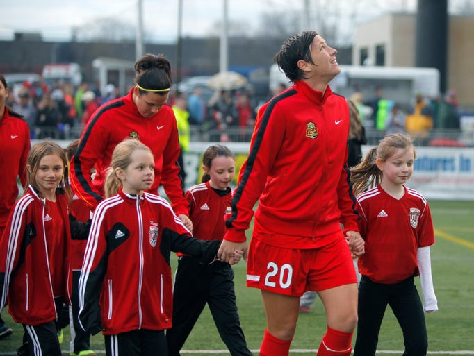 Flash star Abby Wambach leads youngsters onto the pitch while looking at the sky as clouds move in during the 2014 season.