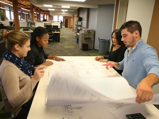 A team at LaBella Associates, from left, Stephanie Dole, marketing coordinator, Ke'Shara Webb, junior civil engineer, Karen Monserrate, administrative assistant, and Jim Messana, junior civil engineer, look over a project in a conference area at LaBella in downtown Rochester Wednesday, Nov. 16, 2016.