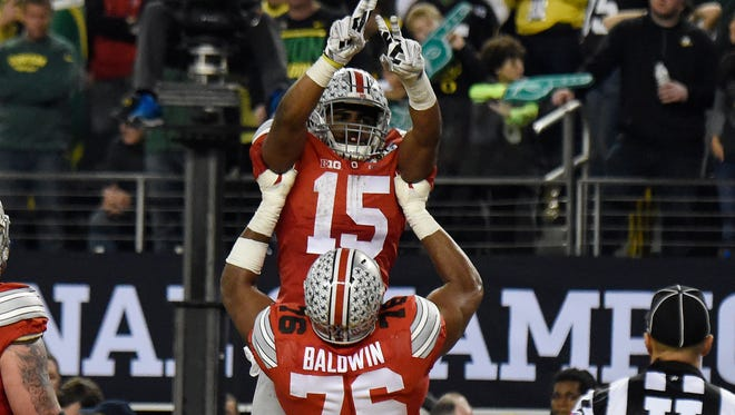 Ohio State Buckeyes running back Ezekiel Elliott (15) celebrates a touchdown during the third quarter against the Oregon Ducks in the 2015 CFP National Championship Game at AT&T Stadium.