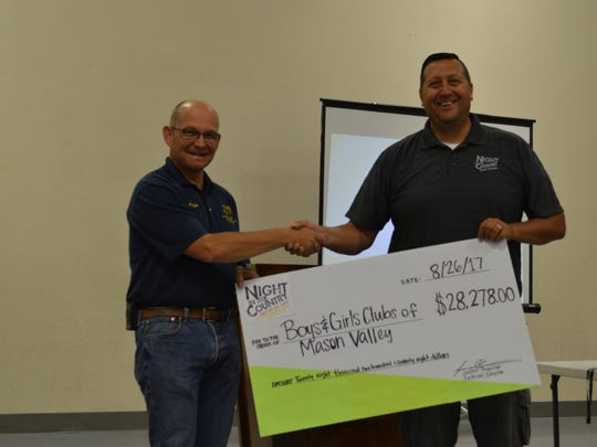 Lyon County Manager Jeff Page (left) receives a check from Night in the Country Festival Director Justin Aguilar.