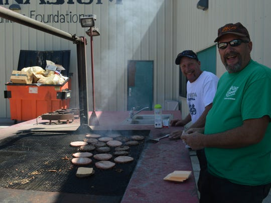 Larry Shipley and Don Veil grill burgers at Night in the Country's volunteer appreciation lunch.