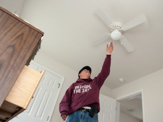 Bill Mullen adjusts a ceiling fan in one of the bedrooms on the second floor of his new home in December 2015.