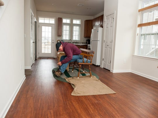 Bill Mullen ties his boot in the kitchen/dinette area of his new home in December 2015.