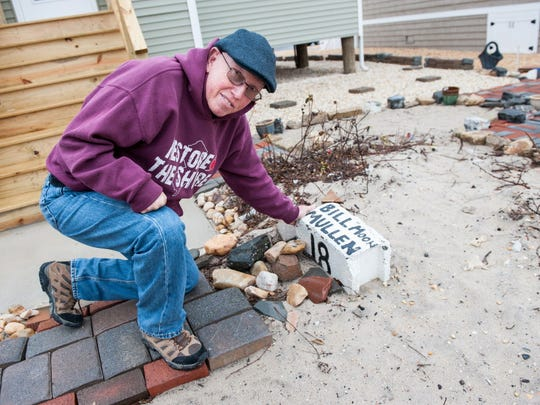 Bill Mullen shows a cinder block from 1948 that has his father's name on it. The cinder block was uncovered after Sandy and was originally on the home at 20 Coolidge which his father owned. This photo was taken in 2015.