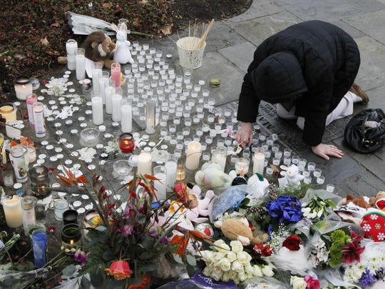 A woman pays respects at a memorial outside of St. Rose of Lima Roman Catholic Church, Sunday, Dec. 16, 2012, in Newtown, Conn. On Friday, a gunman allegedly killed his mother at their home and then opened fire inside the Sandy Hook Elementary School in Newtown, killing 26 people, including 20 children.
