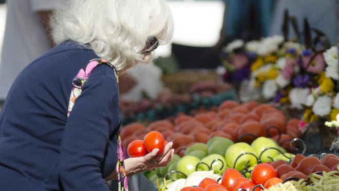 A woman selects tomatoes at the Minnetrista Farmers Market.