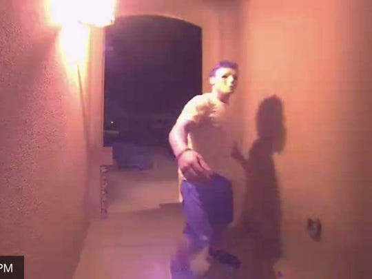 A masked person rings a doorbell at a Sonoma Ranch area home at 11:32 p.m. on July 24, 2017.