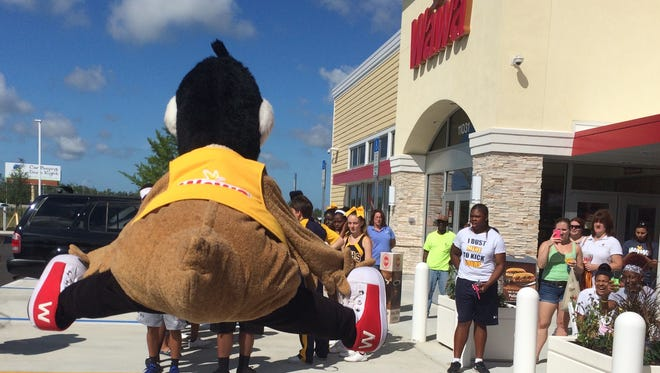 Wally Goose, Wawa's mascot, jumps into the air before doing the splits at an impromptu dance battle Thursday at the newest Wawa store in Fort Myers.