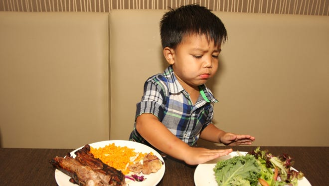 Cameron Catindig, 2, pushes away a plate of leafy greens in favor of some meat and rice. When dealing with picky eaters, moms suggest getting creative to make healthy foods tastier, teaching kids good eating habits and sneaking in the good stuff.