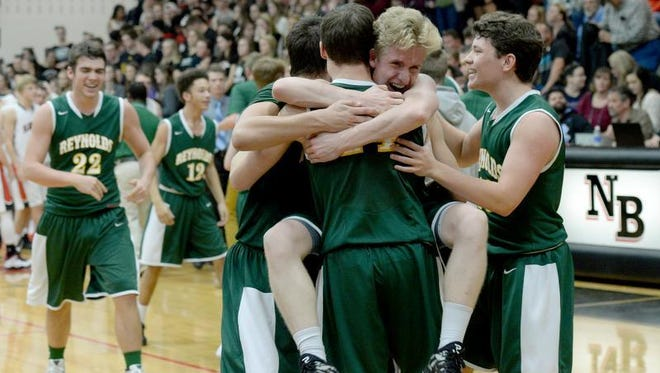 Reynolds' Zack Brown leaps into the arms of his teammates after they won the Mountain Athletic Conference 3-A basketball tournament on Friday night in Weaverville.