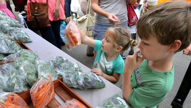 Olivia Rutherford, 3, picks out a bag of carrots as her brother, Adron, watches at the first Main Street Saturday Market of the 2014 season on the Public Square.
