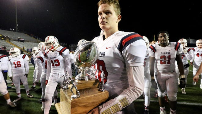 Oakland's quarterback Brendan Matthews (10) holds the 2nd place team trophy as he and the team react to the losing to Whitehaven in the 6-A State Championship Game on Saturday, Dec. 3, 2016, in Cookville, Tenn..