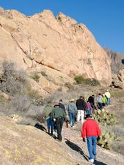 Hikers head up the winding trail to Hermit's Cave at