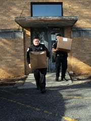 Anderson County Sheriff's Office deputies Caleb Carroll, left, and Jonathan Villegas carry boxes of Thanksgiving turkeys and fixings for needy families.