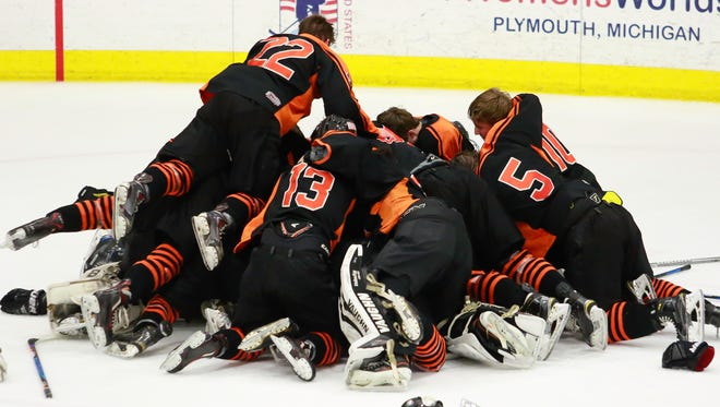 Brighton players celebrate a state Division 1 hockey championship after beating Detroit Catholic Central, 5-2.