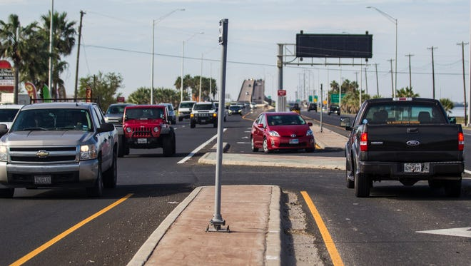 Andrew Mitchell/Caller-Times Vehicles drive eastbound along Park Road 22 while two vehicles wait in their turnaround lanes at the intersection of Aquarius street in January 2015.