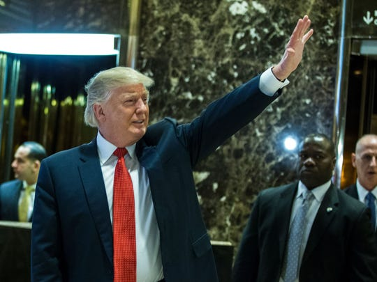 President-elect Donald Trump waves to the crowd as he exits the elevators to speak with media at Trump Tower on Dec. 6, 2016, in New York.