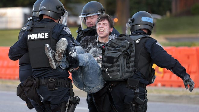 Florissant police officers carry away a woman after she was arrested while officers were trying to confiscate painting equipment Sunday across the street from the police department. Protesters had just started re-painting 'Black Lives Matter' on Lindbergh Boulevard when officers came out of the station and began taking their rollers and paint cans.