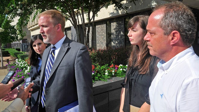 Chris Coleman with the Tennessee Justice Center, second from left, talks with the news media outside the Estes Kefauver Federal Building in Nashville after a hearing Friday. Plaintiffs Derek Simpson, right, and Terri Lynn Casola look on.