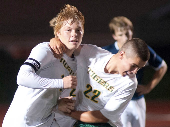 St. X's Colin Kremer, right, wraps his arms around teammate Joe Workman after Workman scored the second goal of the game. St. Xavier scored two goals in the second half to defeat Collegiate, 2-0. Oct. 16, 2013