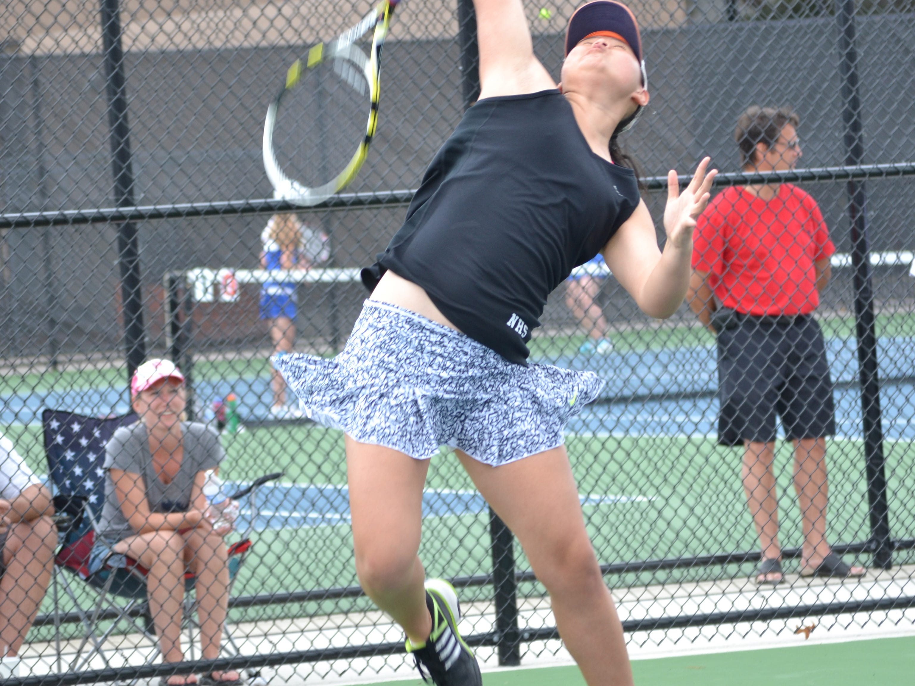 Northville's No. 2 doubles player Claudia Ma goes for the over-head smash in Saturday's KLAA Association 'A' tournament.