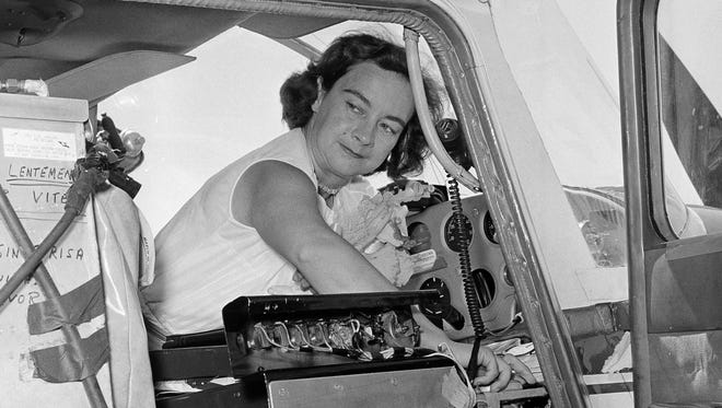 FILE - This photo made April 16, 1964, shows Jerrie Mock checking her extra gas tank cap just before taking off from Oakland Airport, in Oakland, California.