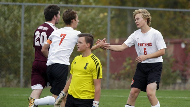 Plymouth's Aidan Woida (7) and Dylan Koehn (6) celebrate the Panthers' first goal as Winneconne goalkeeper Daniel Knitt (1) reacts to the play during the first half on Tuesday.