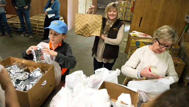 Beth Stahl, center, creator of the MANNA Packs for Kids program with the MANNA Food Bank, holds the 1 millionth bad of food bound for a needy child's home while volunteers pack food Wednesday afternoon at the MANNA volunteer station on Tunnel Road. Stahl created the program 10 years ago to help fill the need for a 16-county radius.