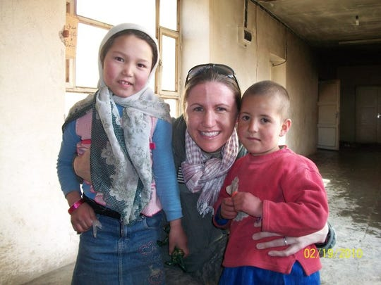 Army Capt. Marjorie Eastman with two children during a 2010 mission to deliver cold-weather supplies to an orphanage in Banyan Province in Afghanistan