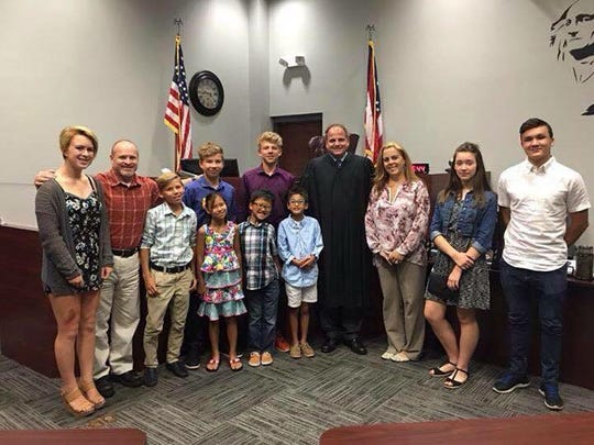 Tracy Snyder and her husband, Butch, with their nine children along with Warren County Probate Judge Joseph Kirby.