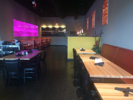 There is table and booth seating inside of Komoon Thai