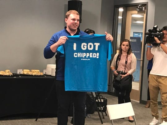 "An employee at Three Square Market in River Falls, Wisc., displays an ""I Got Chipped"" T-shirt at a company function where management embedded microchips in employees."