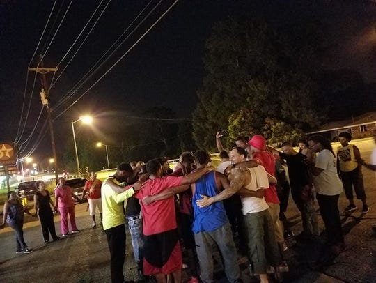 A prayer circle forms during a peace walk in Lafayette